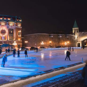 People on the outdoor ice rink at Place D'Youville, near the Capitol, the fortifications and the illuminated Saint-Jean gate.