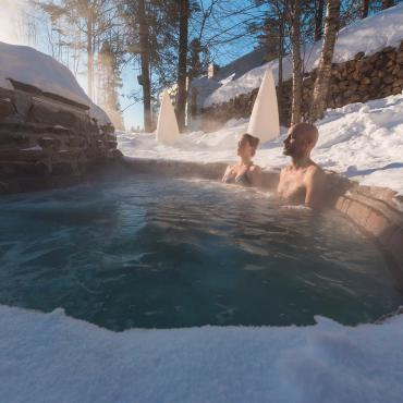A couple relaxes in a Nordic spa in winter.