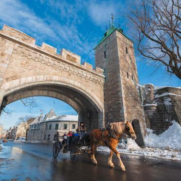 Two tourists in horse-drawn carriages pass under the Saint-Louis Gate in winter.
