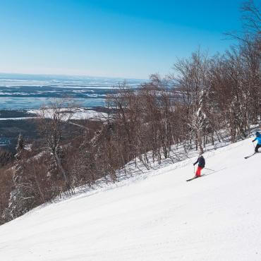 Two skiers go downhill skiing at Mont-Sainte-Anne station with a view of the St. Lawrence River.