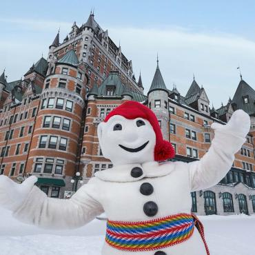 Bonhomme Carnaval poses proudly on the snow-covered Dufferin terrace, in front of the Château Frontenac.