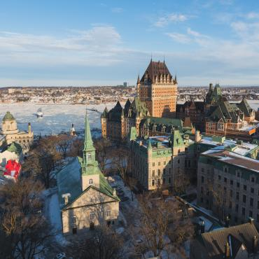 Aerial view of Old Québec in winter, with the frozen St. Lawrence River, Château Frontenac and Holy Trinity Church.