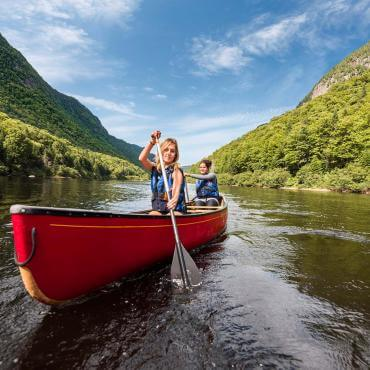 Two young women canoe in the river at the bottom of the valley, in Jacques-Cartier National Park.