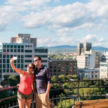 A couple takes a photo at the top of the Faubourg staircase with a view of the Saint-Roch district in the background.