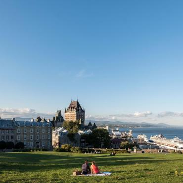 Couple picnic near the Pierre-Dugas-De Mons terrace, in front of a panorama of Old Québec and the St. Lawrence River.