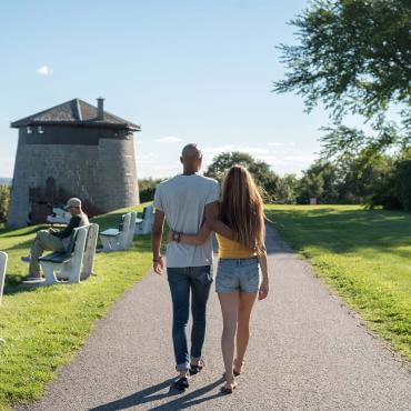 Couple in love walking on the Plains of Abraham, towards the Martello Tower 1, in summer.