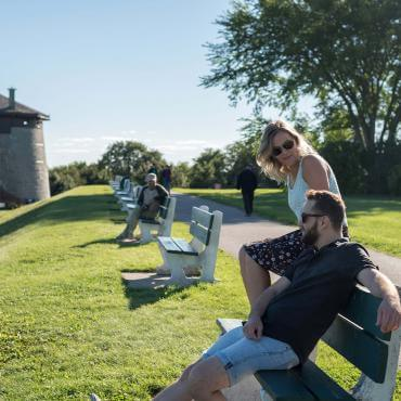 Couple sitting outside on a bench, near Martello Tower 1, on the Plains of Abraham.