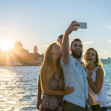 Friends take pictures of themselves at sunset, near the St.Lawrence River in Lévis with a panorama of Old Québec in the back.