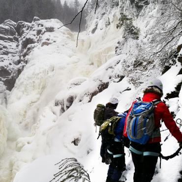 A group of people do the winter Via Ferrata activity at Canyon Sainte-Anne.